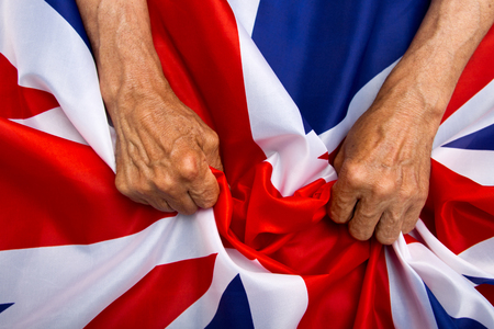 divide: Elderly man hands holding a UK flag. The concept of caring for pensioners. Stock Photo