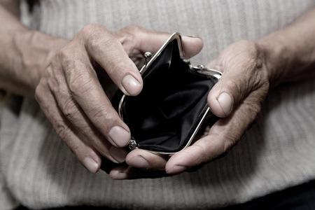 Un anciano sostiene un bolso vacío. El concepto de pobreza en la jubilación.