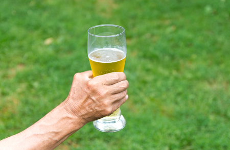 fatness: The beer glass in the hand of an elderly man. Alcohol consumption in old age. Beer alcoholism.
