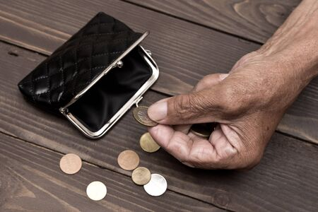 An elderly person holds the coins over the old empty wallet. The concept of poverty in retirement. Stock Photo