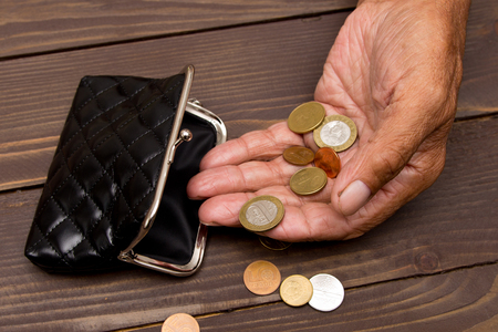 billfold: An elderly person holds the coins over the old empty wallet. The concept of poverty in retirement. Stock Photo