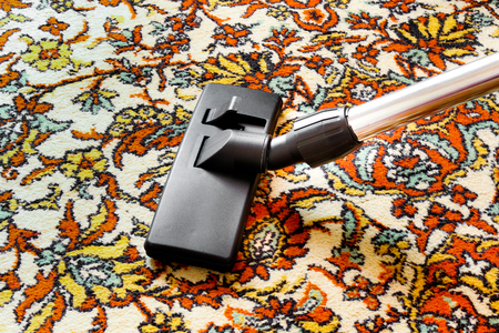 Cleaning old carpet with a vacuum cleaner universal nozzle Stock Photo