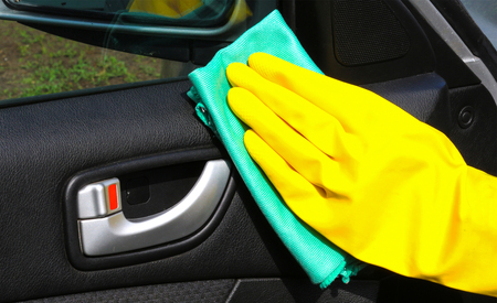Hand Cleaning Interior Car Door Panel With A Green Microfiber