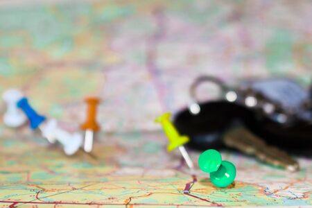 Travel destination points on a map indicated with colorful thumbtacks and shallow depth of field with space for copy. The keys to the car in the blur in the background. Stock Photo