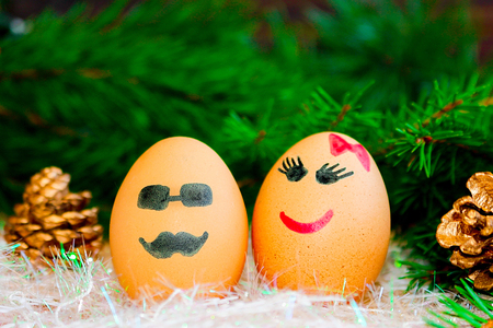 Two lovers celebrate Christmas . Unusual eggs with the muzzle. Two eggs the love . The cartoon Christmas decorations Stock Photo
