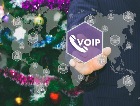 The businessman chooses VOIP on the touch screen, the backdrop of the Christmas tree and decorations. Special toning .