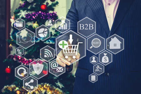 photo the businessman chooses the shopping cart on the touch screen the backdrop of the christmas tree and decorations special toning cyber monday