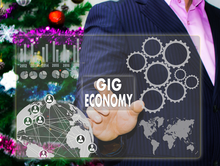 The businessman chooses GIG ECONOMY on the touch screen, the backdrop of the Christmas tree and decorations. Special toning .
