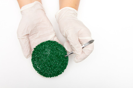 Plastic pellets . Colorant for polymers in granules. Worker wearing gloves takes plastic pellets with tweezers. Stock Photo