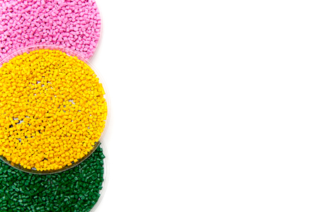 Plastic pellets green yellow and pink . Colorant for polymers in granules. Template Stock Photo