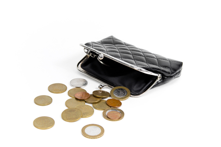 Coins from the old wallet on a white background. Vintage empty purse. The concept of poverty in retirement. Stock Photo