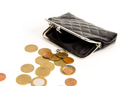 Purse for coins. Open wallet with coins. Coins spilled on a white table