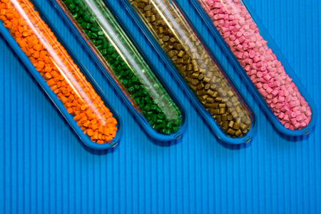 Plastic pellets .Polymeric dye in test tubes on blue corrugated background. Stock Photo