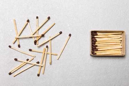 The concept of chaos and order. Chaotic match boxes lying around with the order of stacked matches Stock Photo