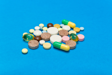 Opioid Pills. Colored pills on a blue background.Problem Opioid epidemic . Stock Photo