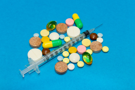 Opioid epidemic .Opioid Pills. Drug abuse Concept - different colored pills and syringe on a blue background. Stock Photo
