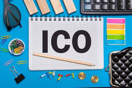 A Notebook with Business notes initial coin offering ICO with office tools on blue background. Concept of the choice ICO Stock Photo