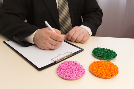 Businessman signs a contract for the supply of plastic granules for industry. Plastic raw material in granules . Polymer, plastic resin. Banco de Imagens