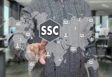 An elderly pensioner chooses SSC, service Center around the world on the touch screen on blur office background.