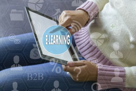 E-LEARNING on the touch screen with a blur the girl with the gadget background .The concept of E-LEARNING