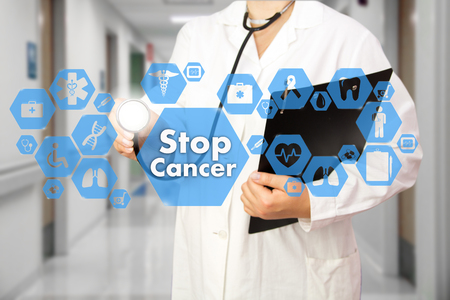 Medical Doctor with stethoscope and Stop Cancer sign in Medical network connection on the virtual screen on hospital background.Technology and medicine concept. Stock Photo