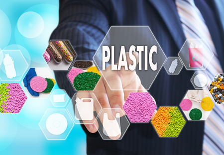 The businessman chooses PLASTIC on the virtual screen in plastic industrial network connection.The concept of raw material plastic in granules