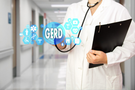 Medical Doctor with stethoscope and word GERD, Gastroesophageal reflux disease in Medical network connection on the virtual screen on hospital background.Technology and medicine concept.