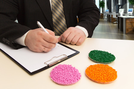 Businessman in the office signs a contract for the supply of plastic granules for industry. Plastic raw material in granules . Polymer, a plastic resin.Granules of polypropylene and polyethylene.