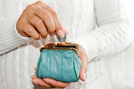 Young woman putting coin in purse. Leather purse for coins.Wallet in hand . Poverty