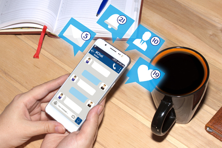 Hands holding smartphone with chat interface and icons from social media.