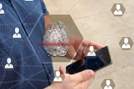 Fingerprint scanning on the touch screen with a blur background of the businessman with the phone.The concept of Secure access through fingerprint scanning to the network