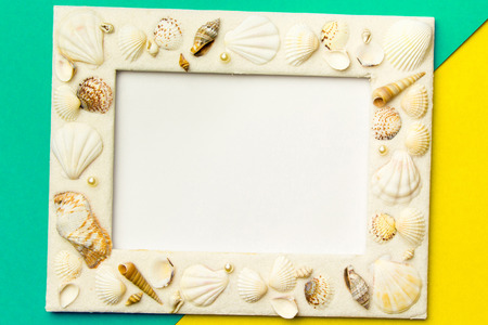 Photo frame with shells on turquoise and yellow color paper texture background. The concept of a summer vacation.  Summer Flatlay Image