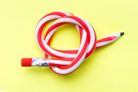 Flexible pencil on a yellow background. Bent pencils two-color