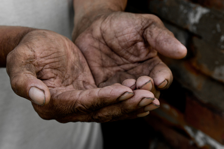 The poor old mans hands beg you for help. The concept of hunger or poverty. Selective focus. Poverty in retirement. Alms