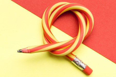 Flexible pencil on a textured cardboard background. Bent pencils two-color