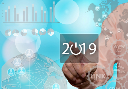 An elderly businessman chooses 2019 year on the touch screen with a blur office background .Starttap, webinar, new projects, pibyl in the new year Stock Photo