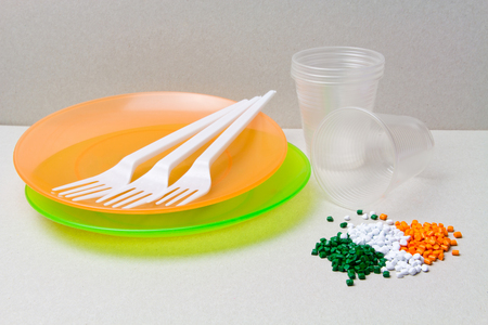 Polyethylene granules and disposable tableware made of polyethylene, polypropylene. Plastic Raw material and its products Stock Photo