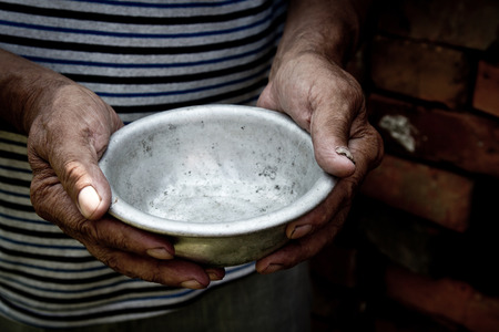 The poor old mans hands hold an empty bowl. The concept of hunger or poverty. Selective focus. Poverty in retirement.Homeless. Alms