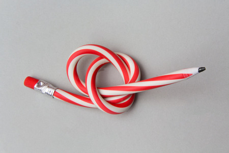 Flexible pencil on a grey background. Bent pencils two-color Stock Photo
