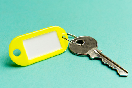 Yellow key tag on a turquoise textured cardboard background.The concept of rent, selling. Template. Trend colors