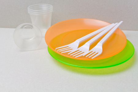 Plastic disposable tableware made of Plastic Raw material, polyethylene, polypropylene. BPA FREE concept. Disposable tableware background. Stock Photo