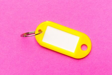 Yellow key tag on purple cardboard textured background.The concept of renting, selling. Template. Trend colors