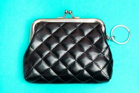 Purse for coins. Black leather wallet on blue background