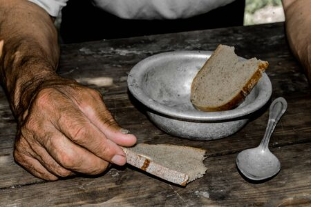 Hands the poor old mans, piece of bread and empty bowl on wood background. The concept of hunger or poverty. Selective focus. Poverty in retirement.Homeless. Alms