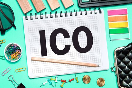 A Notebook with Business notes initial coin offering ICO with office tools on blue background. Concept of the choice ICO Reklamní fotografie