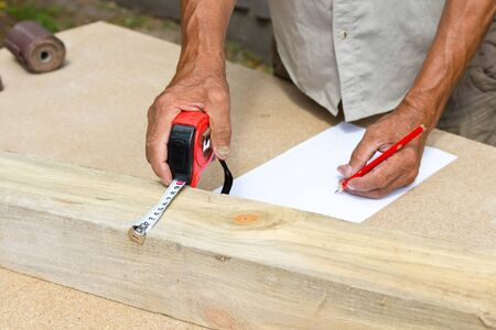 Carpenter inspect the quality of the material and calculate the required quantity for production .Manufacturing of furniture from a natural tree.Employee Uses technology to benefit