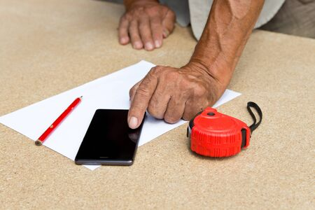 Carpenter uses smartphones to calculate the required materials and contacts customers .Employee Uses technology to benefit. Stock fotó - 126307981