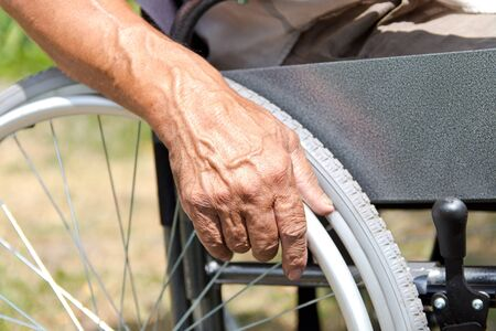 A disabled man is sitting in a wheelchair ,Holds his hands on the wheel. Handicap people Concept.