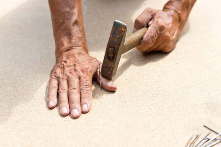 L'uomo ha colpito il dito con un martello. Falegnameria professionale, falegnameria e persone. concetto di infortunio sul lavoro. Copia spazio