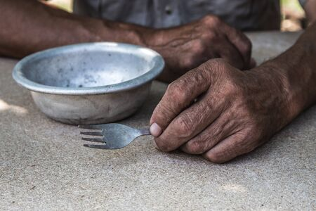 Hungry. Poor old mans hands an empty bowl. Selective focus. Poverty in retirement. Alms